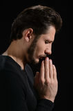 The power of prayer. Side view of bearded man praying and holdin Royalty Free Stock Images