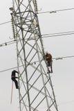 Power pylon. Workers climbing on power pylon Stock Images