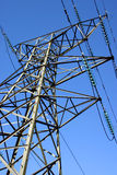 Power Pylon. British electricity pylon carrying national grid high voltage power cables; photographed against a blue sky Royalty Free Stock Images