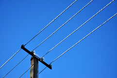 Power pylon cable under blue sky Stock Photography