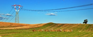 Power pylon and hay bales Royalty Free Stock Photography