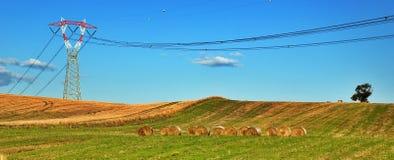 Power pylon and hay bales royalty free stock photography