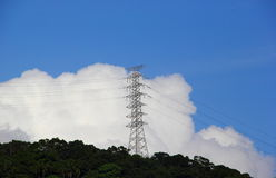Power pylon over the hill. Against white cloud and blue sky Royalty Free Stock Photos