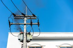 Power pylon overload or electric short circuit at transformer on poles and fire or flame with smoke on blue sky.  stock image