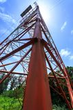 Power pylon. Super wide angle photograph of Electricity pylon with blue sky and sun Royalty Free Stock Photo