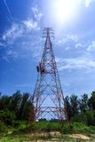 Power pylon with trees and blue sky and white clouds Royalty Free Stock Images