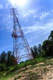 Power pylon with trees and blue sky and white clouds Stock Photography