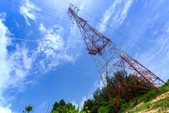 Power pylon with trees and blue sky and white clouds Stock Image