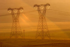Power pylons. Backlit power pylons in mist at sunset Royalty Free Stock Photography