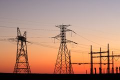 Power pylons. Silhouetted power pylons against a red sky at sunset Royalty Free Stock Images
