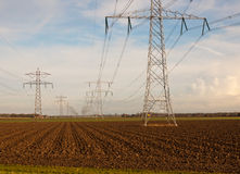 Power pylons in an agricultural Dutch landscape Royalty Free Stock Photo