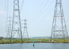 Power pylons by the shore Royalty Free Stock Images