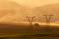 Power pylons at sunset. Backlit power pylons in mist at sunset Stock Images