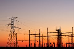 Power pylons at sunset. Silhouetted power pylons against a red sky at sunset Stock Image