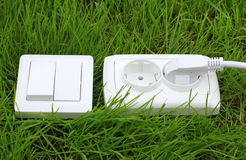 Power receptacle and light switch on a green grass Stock Photos