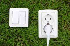 Power receptacle and light switch on a green grass Stock Photo