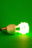 Power-saving light-bulb on green background. A modern power-saving light-bulb lit on green background Stock Images