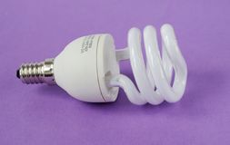 Power saving up lamp. Small power saving up lamp on violetbackground Royalty Free Stock Photography