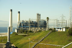 Power by the sea. A power plant on a hill by the sea with smokestacks Stock Image