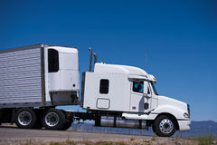 Power Semi truck rig and reefer trailer side view Royalty Free Stock Photography