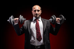 Power. A serious businessman wearing a suit and lifting two heavy weight Stock Images