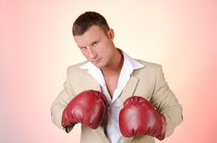 Business and success. Office fight. Young man in boxing gloves. Work and the battle. Power and sexy. Fitness and healthy lifestyle. Sport and diet Stock Images
