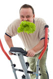 Power slimming concept - isolated. Power slimming concept with overweight man on exercise machine eating fresh green salad - isolated Royalty Free Stock Image