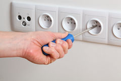 Power socket. Man's hand with screwdriver repairing a socket Stock Photo