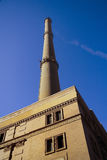 Power station. With chimney on the blue sky in the background Royalty Free Stock Photography