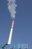 Power station chimney. Smoking power station chimney under clear blue sky Royalty Free Stock Photos