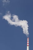 Power station chimney. Smoking power station chimney under clear blue sky Royalty Free Stock Images