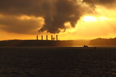 Power station on the coast at sunrise Stock Photos