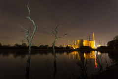 Power Station And Dead Trees. A coal-fired power station in river landscape with dead trees at night Royalty Free Stock Photography