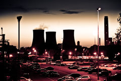 Power station at dusk. Power plant at dusk, showing pollution Stock Image