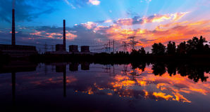 Power station at dusk reflection in the water, and power lines at sunset. Stock Images