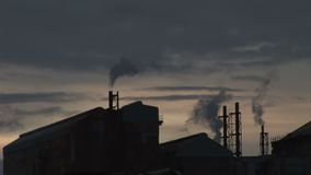 Evening at power station dark sky pollution. Power station in the evening as smoke goes into the sky stock video footage