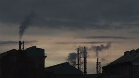 Evening at power station dark sky silhouette smoke comes out of chimney. Power station in the evening as smoke goes into the sky stock video