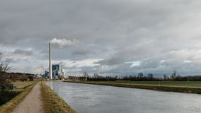 Power station with high chimney. High chimney on power station and road near the river, cloudy sky stock photos
