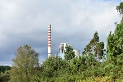Power station in landscape. White and red long smoking chimney, industry and nature. Trees, grass, bushes and cloudy sky. stock photo