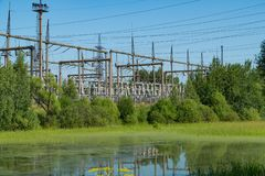 Power station near the pond. Power lines. Royalty Free Stock Image