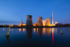 Power Station At Night. A coal-fired power station in river landscape with dead trees at night Stock Images