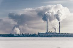 Power station with pipes of which poured smoke on a frozen river. Free copyspace Royalty Free Stock Image