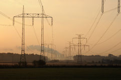 Power station in smog. Behind columns of power line Stock Photos