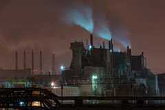 Power station with steam cloud blown by the wind. In a cold starry winter night Royalty Free Stock Images