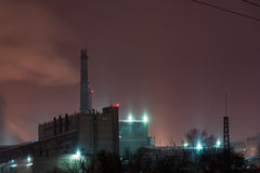 Power station with steam cloud blown by the wind. In a cold starry winter night Royalty Free Stock Photography