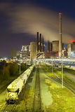 Power Station And Train At Night. A brown coal power station with night blue evening sky and a train in the foreground royalty free stock image
