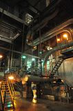 Power 2. Steel stairs and snaking silver pipe in the complex system of pipes, valves and boilers in a coal burning electricity generating plant Royalty Free Stock Image
