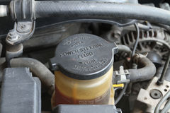 Power steering fluid cap. With warning label in a car Stock Photo