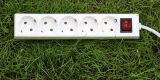 An power strip lying on the grass Stock Image