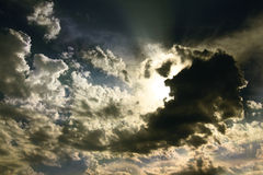 THe Power of Sunshine. A powerful beam of sun illuminating a dramatic piece of sky with scattered clouds Royalty Free Stock Photography
